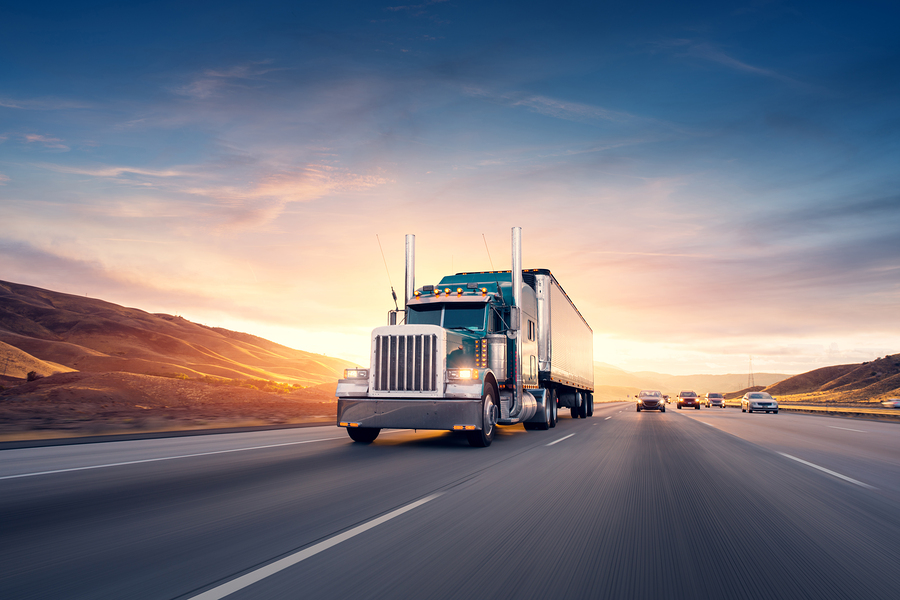 American style truck on freeway pulling load. Transportation theme. Road cars theme.: American style truck on freeway pulling load. Transportation theme. Road cars theme.