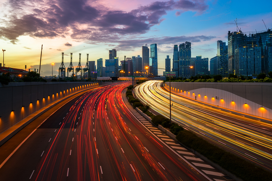Night City Road With Traffic Headlight Motion In The City: Night city road with traffic headlight motion and city skyline background. Cityscape in Singapore city. Busy road city and highway in Singapore central area. Light up road by vehicle motion blur.